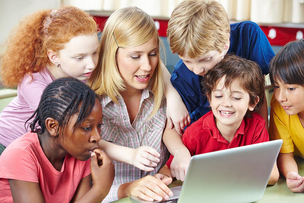 Children and teacher around laptop